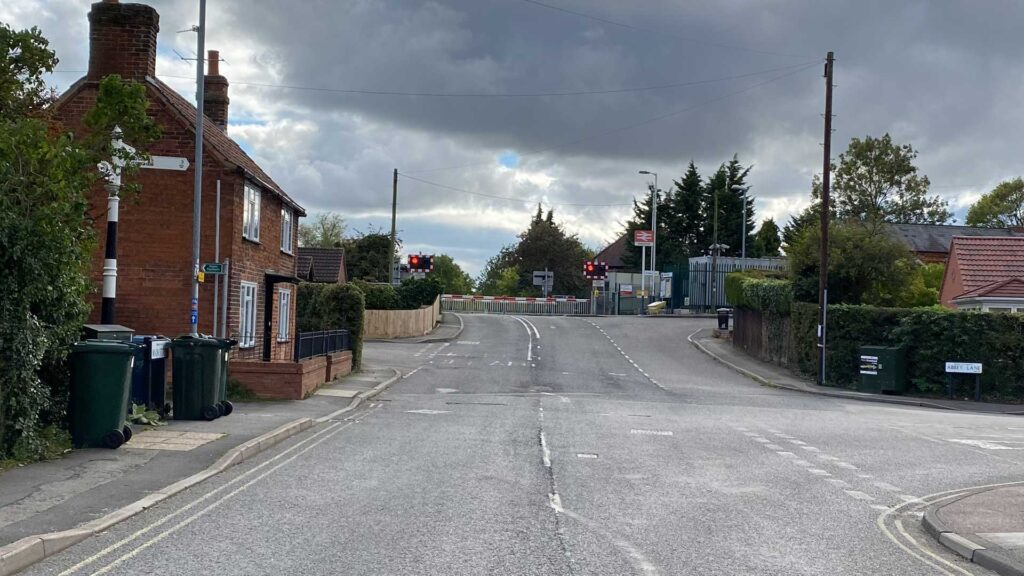 The level crossing on Main Street, Aslockton, the barrier down and lights flashing.