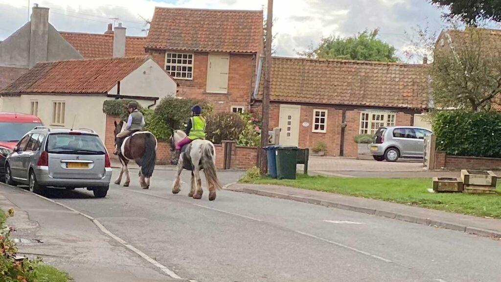 Horses amble sedately down Main Street, Aslockton.